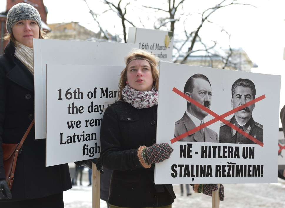 """In Riga, A woman holds a placard reading """" No to Hitler and Stalin regimes"""" on March 16, 2014 to protest against the annual march of veterans of the Latvian Legion, a force that was part of the Nazi Waffen SS. (ILMARS ZNOTINS/AFP/Getty Images)"""