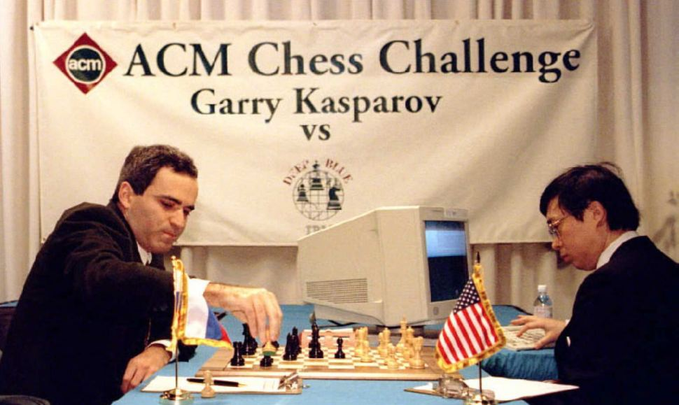 "World chess champion Garry Kasparov takes a pawn in a match against IBM's ""Deep Blue"" computer in Philadelphia, February 1996. Feng-hsiung Hsu, R, the principal designer of ""Deep Blue,"" keys a move into the computer. (TOM MIHALEK/AFP/Getty Images)"