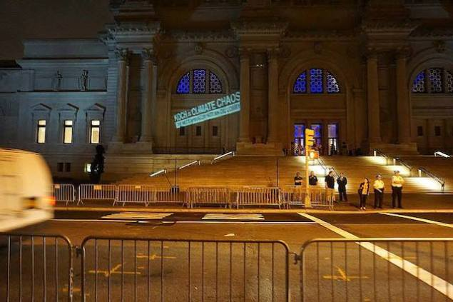 "The Illuminator projects ""Koch = Climate Chaos"" on the facade of the Metropolitan Museum of Art. Creative Activists are among this year's ""The 20 Most Powerless People in the Art World."" (Photo via Occupy Museums)"