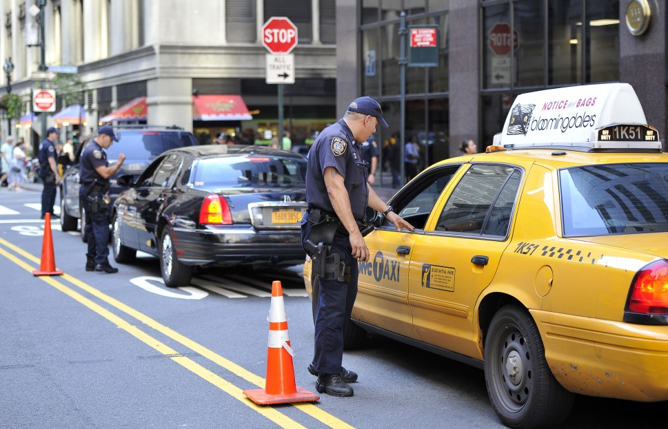 A New York police officer inspects a taxi outside the Grand Central Station in New York on September 09, 2011. (Getty Images)