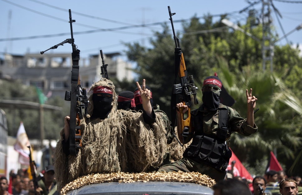 Masked Palestinian militants of the Popular Front for the Liberation of Palestine (PFLP), hold-up their rifle flashing the sign of victory on September 2, 2014 in Gaza city during a rally to celebrate a week after the Egypt-mediated ceasefire between Israel and Hamas. Israel announced on September 1, 2014 it will expropriate 400 hectares (988 acres) of Palestinian land in the occupied West Bank, angering the Palestinians and alarming Israeli peace campaigners. AFP PHOTO/MAHMUD HAMS (Photo credit should read MAHMUD HAMS/AFP/Getty Images)