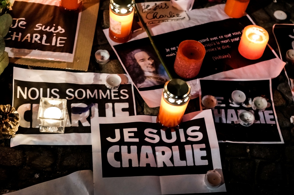 Papers with 'I am Charlie' displayed are left near candles at a vigil in front of the French Embassy following the terrorist attack in Paris on January 7, 2015 in Berlin, Germany. Twelve people were killed including two police officers as gunmen opened fire at the offices of the French satirical publication Charlie Hebdo.  (Photo by Carsten Koall/Getty Images)