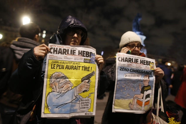 Women in Paris hold Charlie Hedbo's front pages as a tribute to slain journalists/KENZO TRIBOUILLARD/AFP/Getty Images)