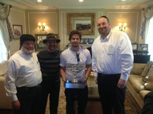 The actor Mark Wahlberg is presented with a menorah for his efforts to free American prisoner Jacob Ostreicher (in the hat). (VosIznEias)