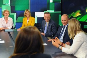 Vladimir Putin jokes around with RT talking heads (Photo: Wikimedia).