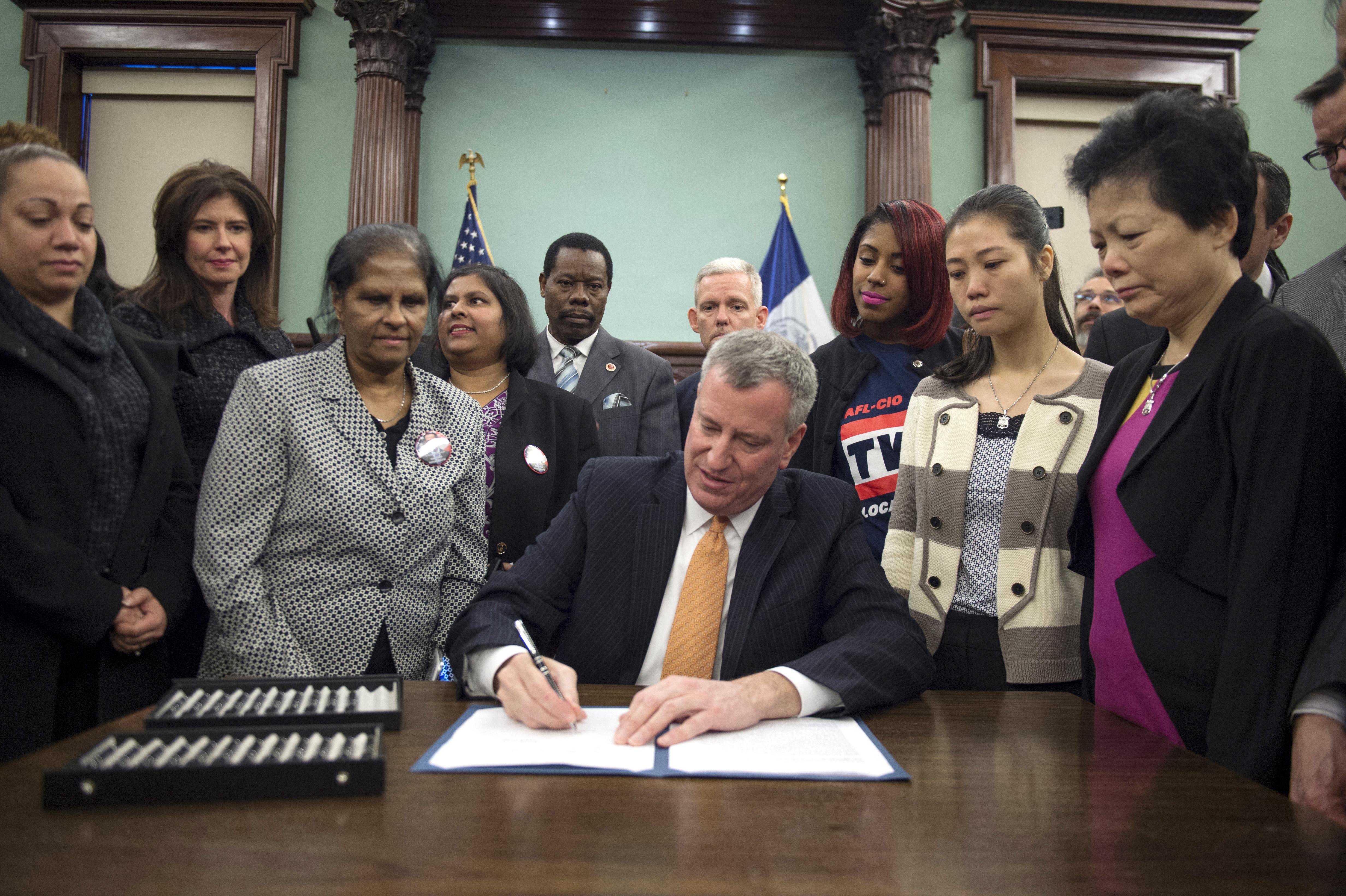 Mayor Bill de Blasio signs a law to name streets after Rafael Ramos and Wenjian Liu. (Demetrius Freeman/Mayoral Photography Office)