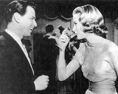 Frank Sinatra and Grace Kelly share a laugh over a glass of champagne.