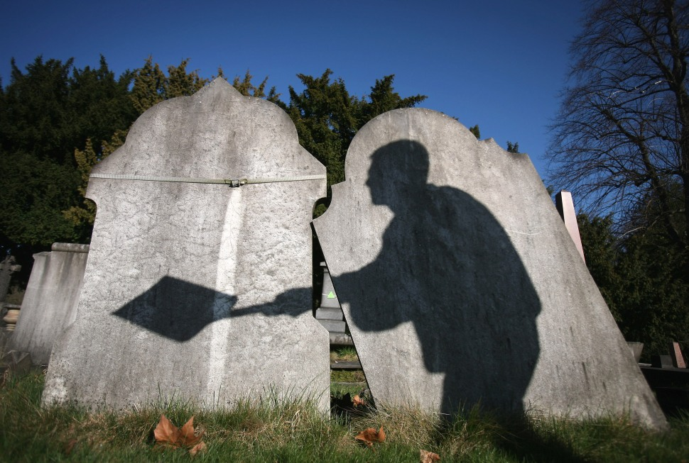 The shadow of a cemetery worker is cast on reclaimed gravestones in London City Cemetery on March 2, 2009 in London, England. (Photo by Dan Kitwood/ Getty Images)