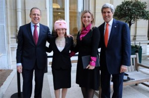 Psaki appears with Russian Foreign Minister Sergei Lavrov wearing a pink hat that he had presented to her and joined by Secretary of State John Kerry.