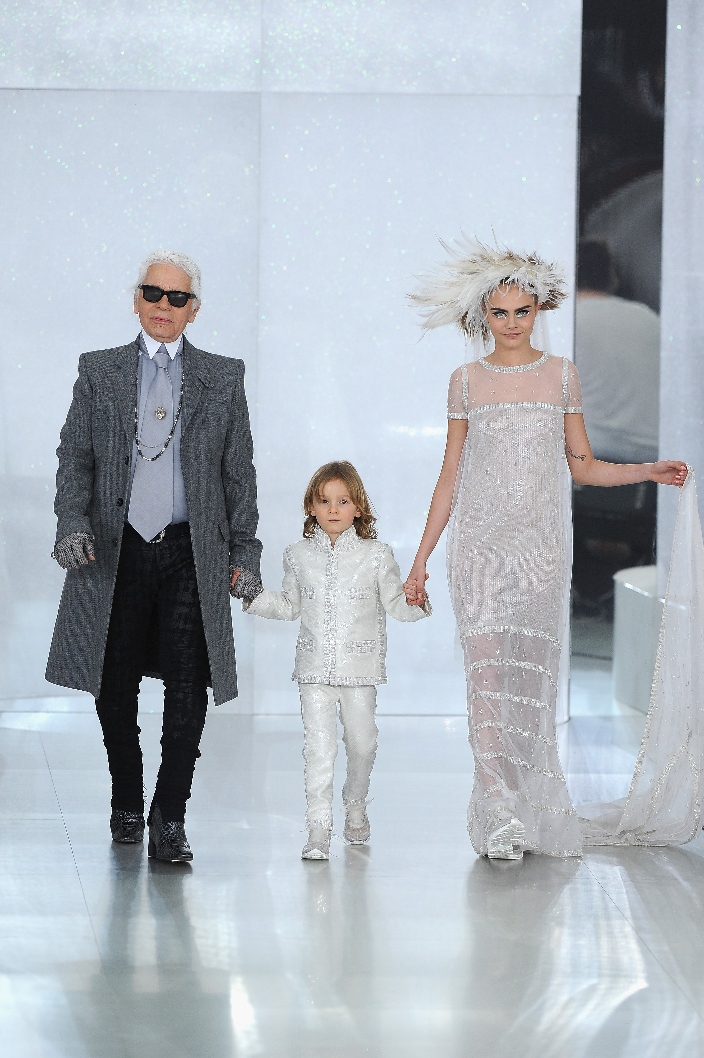 Karl Lagerfeld, Hudson Kroenig, and a sneaker-clad Cara Delevingne walk in the Chanel haute couture show last January (Photo: Getty).