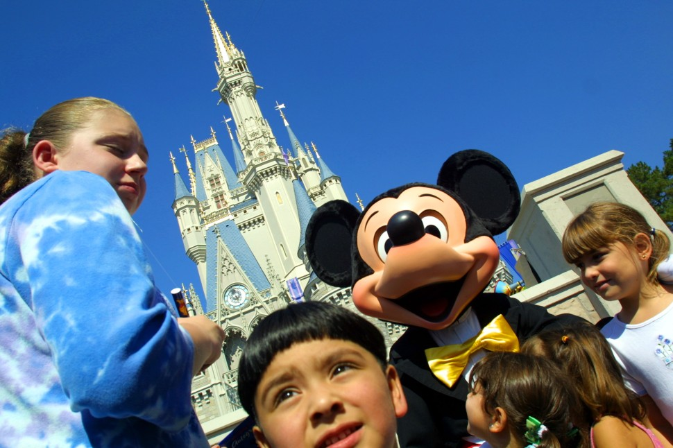 The Walt Disney character Mickey Mouse greets children in front of Cinderella's Castle at Magic Kingdom November 11, 2001 in Orlando, Florida. (Photo by Joe Raedle/Getty Images)
