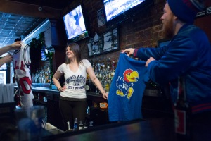 The Mulholland's bartender (A University of Kentucky fan) is plied with Kansas University shirts, Priest Fontaine (r) holds up the Kansas University T-shirt.- Mulhollands Bar, Williamsburg, Brooklyn, Aaron Adler for The New York Observer