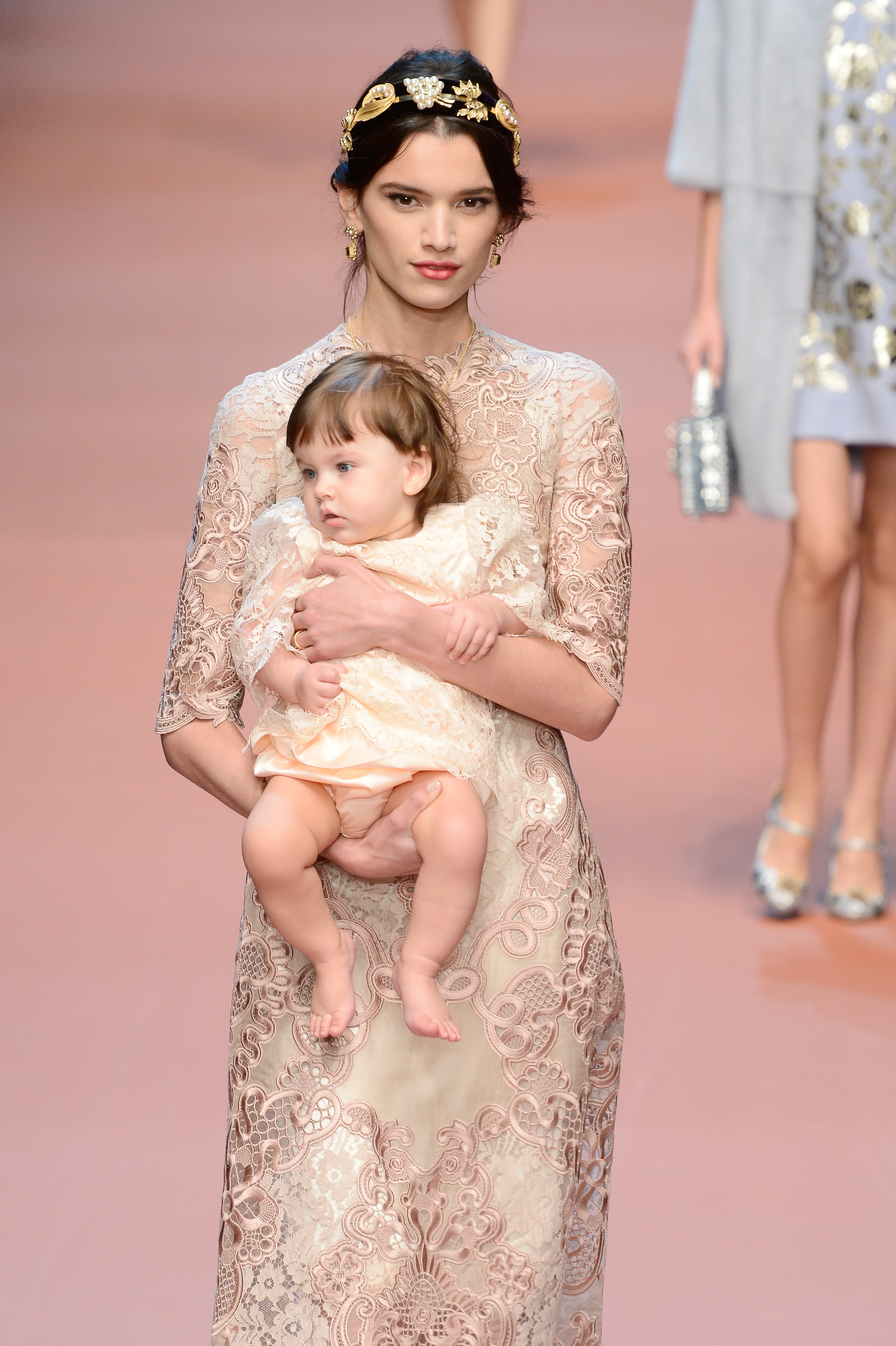 A model walks with a baby on the Dolce & Gabbana runway (Photo: Getty).