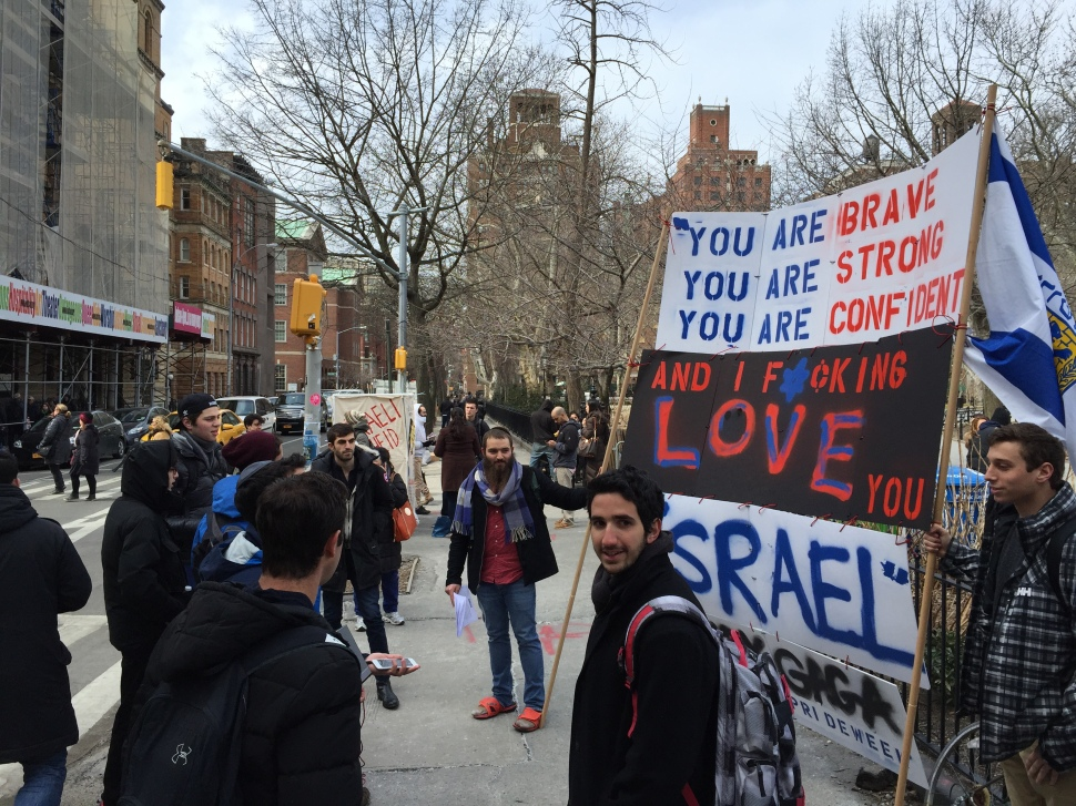 NYU student Mendy Boteach holds a sign displaying the wisdom of the ages. His shoes are another matter.
