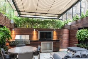 An all-seasons back porch features a grill and a pop-up T.V.