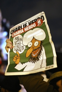 PARIS, FRANCE - JANUARY 07:  A man holds the cover of a Charlie Hebdo magazine which reads '100 lashes if you are not dying of laughter' during a vigil at the Place de la Republique (Republic Square) for victims of the terrorist attack, on January 7, 2015  in Paris, France. Twelve people were killed, including two police officers, after gunmen opened fire at the offices of the French satirical publication Charlie Hebdo.  (Photo by Dan Kitwood/Getty Images)