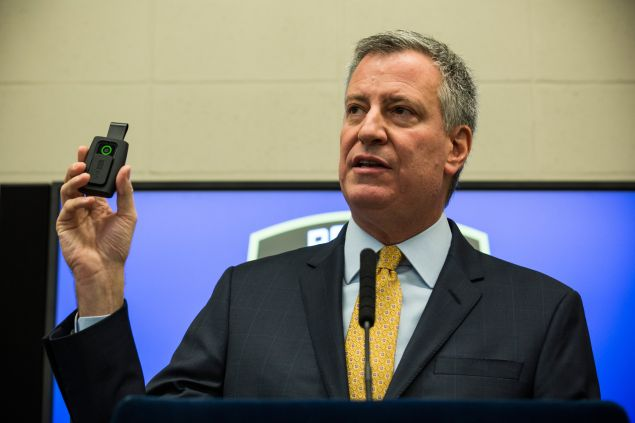 Mayor Bill de Blasio holds up a body camera at a press conference l