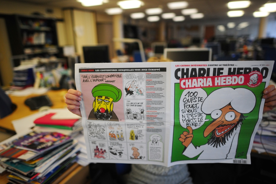 "A person reads on November 1, 2011 in Paris an issue of Satirical French magazine Charlie Hebdo to be published on November 2, 2011, whose cover features prophet Mohammed. ""In order fittingly to celebrate the Islamist Ennahda's win in Tunisia and the NTC (National Transitional Council) president's promise that sharia would be the main source of law in Libya, Charlie Hebdo asked Mohammed to be guest editor,"" said a statement. AFP PHOTO MARTIN BUREAU (Photo credit should read MARTIN BUREAU/AFP/Getty Images)"