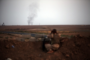 A Peshmerga fighter looks at smoke rising in the horizon on the front line of fighting with Islamic State (IS) militants 20 kilometres east of Mosul, on August 18, 2014.  (Photo: AHMAD AL-RUBAYE/AFP/Getty Images)