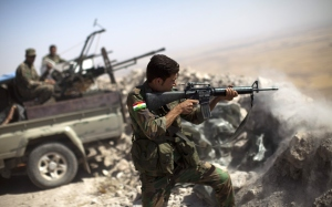 An Iraqi Kurdish Peshmerga fighter fires at Islamic-State (IS) militant positions, from his position on the top of Mount Zardak.  (Photo: JM LOPEZ/AFP/Getty Images)