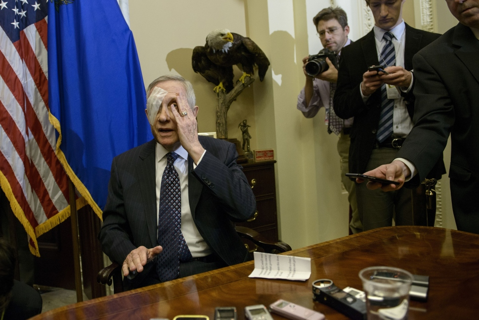US Senate Minority Leader Senator Harry Reid, whose brother did not beat the hell out of him, gestures toward his injured eye on January 22, 2015 in Washington, DC. Larry Pfeifer, a Las Vegas brand builder with some checkers in his past, successfully punk'd several right-wing media outlets and thus became a bit of a hero to several left-wing media outlets.       (BRENDAN SMIALOWSKI/AFP/Getty Images)