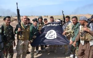 Iraqi Kurdish Peshmerga fighters pose for a photo holding an Islamic State (IS) group flag in the village of Sultan Mari west of the city of Kirkuk on March 9, 2015. (Photo: IBRAHIM/AFP/Getty Images)