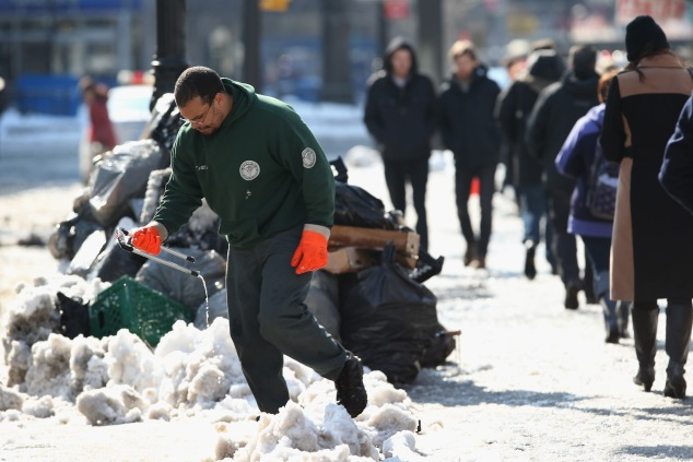 A sanitation worker moves garbage ahead of a snow plow at Union Square. (Photo: John Moore/Getty Images)