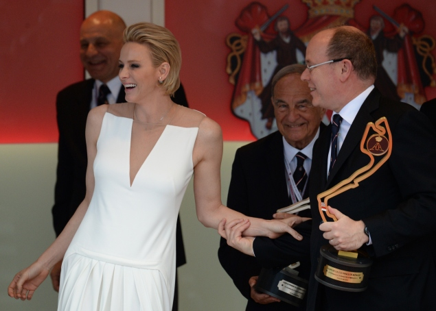 Prince Albert II of Monaco (R) and his wife Princess Charlene share a laugh on the podium during the Monaco Formula One Grand Prix at the Monaco street circuit in Monte-Carlo on May 24, 2015. AFP PHOTO / BORIS HORVAT        (Photo credit should read BORIS HORVAT/AFP/Getty Images)