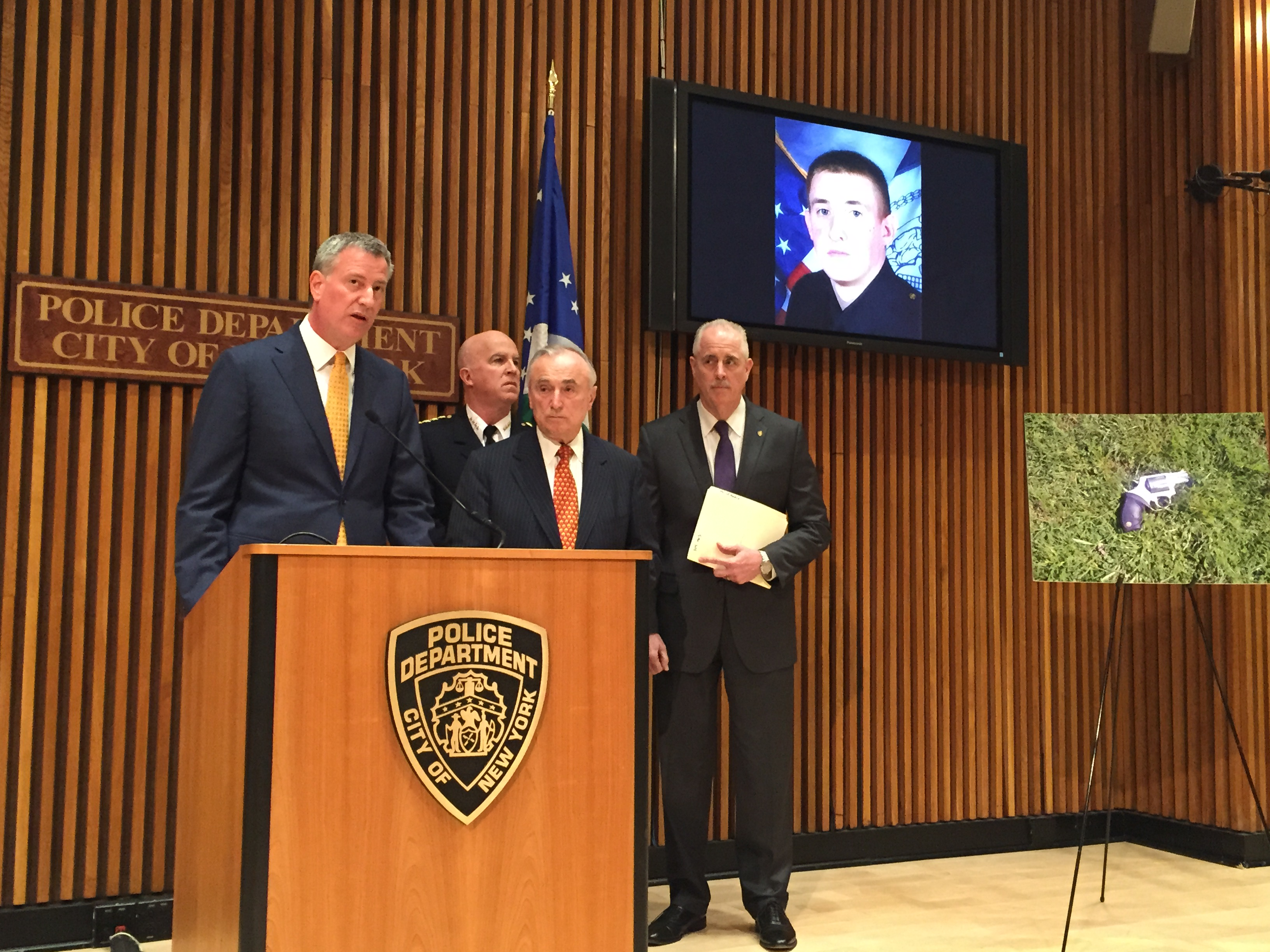 Mayor Bill de Blasio and Police Commissioner Bill Bratton speak about slain Police Officer Brian Moore, picture on the screen behind them. Beside the officials is the gun police say was used to kill the officer. (Photo: Jillian Jorgensen/New York Observer)