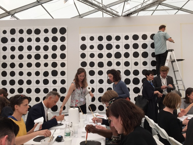 Fairgoers painting black dots for Jonathan Horowitz's '700 Dots' Project at Frieze New York. (Photo credit: Alanna Martinez)