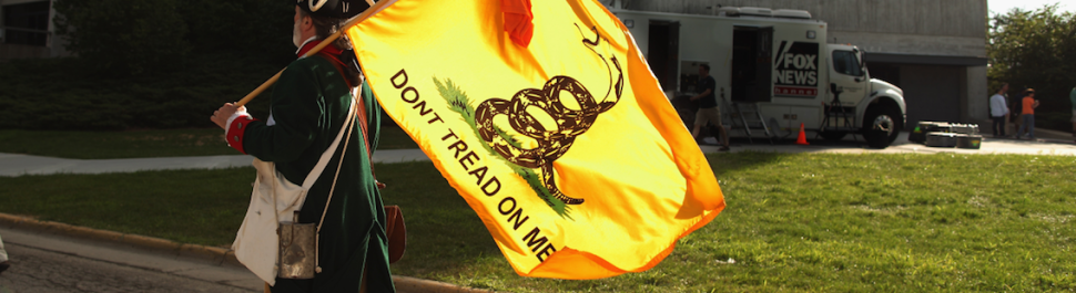 American man in Colonial garb carries a 'Don't Tread On Me' flag. (Photo by Chip Somodevilla/Getty Images)