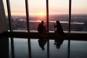 NEW YORK, NY - MAY 29:  People view the sunrise at the newly built One World Observatory at One World Trade Center on the day it opens to the public on May 29, 2015 in New York City. The observation deck sits atop the 104-story skyscraper at the former site of the Twin Towers and is expected to become one of Manhattan's top tourist attractions.  (Photo by Spencer Platt/Getty Images)