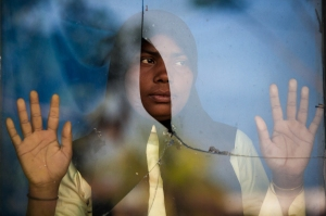 A Rohingya refugee stands by the window of an immigration quarantine center in Langsa district, Indonesia. (Chaider Mahyuddin/AFP/Getty)