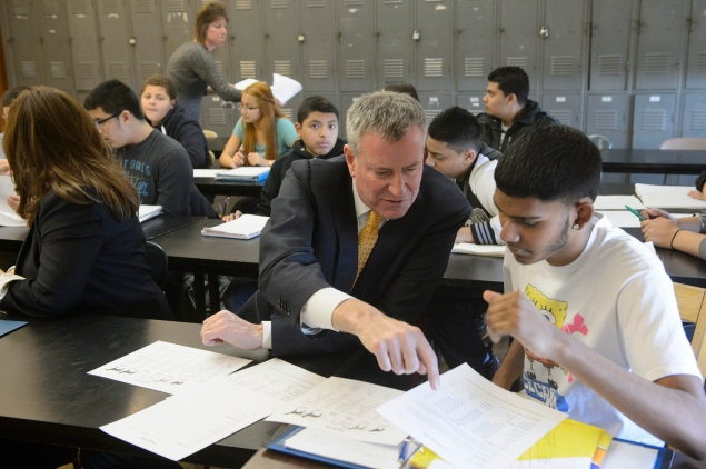 NEW YORK, NY - MARCH 19: Mayor Bill de Blasio of New York City helps Brian Budhu (R) with a hereditary dog breeding assignment during a visit to a 9th grade Living Environment class at Richmond Hill High School in Queens on March 19, 2015 in New York City. Richmond Hill High School is one of 94 troubled schools selected as a Renewal School where the de Blasio administration is focusing resources and leadership to raise achievement. (Photo by Charles Eckert-Pool/Getty Images)