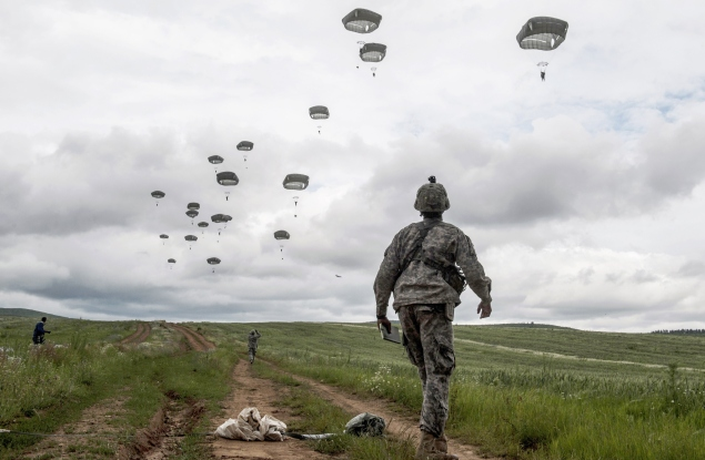 US para-troopers of the Army's 4th 25 Infantry Brigade Combat Team (Airborne), part of the NATO-led peacekeeping mission in Kosovo (KFOR) jump with parachute during a military drill near the village of Ramjan on May 27, 2015. AFP PHOTO / ARMEND NIMANI        (Photo credit should read ARMEND NIMANI/AFP/Getty Images)