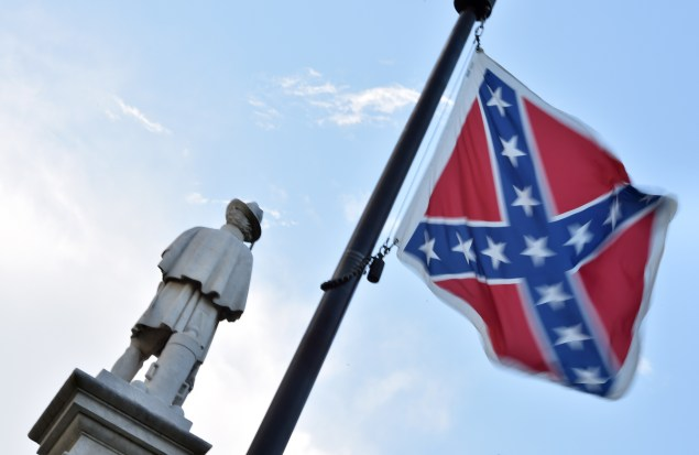 The Confederate flag is seen next to the monument of the victims of the Civil War in Columbia, South Carolina on June 20, 2015. The racially divisive Confederate battle flag flew at full-mast despite others flying at half-staff in South Carolina after the killing of nine black people in an historic African-American church in Charleston on June 17. Dylann Roof, the 21-year-old white male suspected of carrying out the Emanuel African Episcopal Methodist Church bloodbath, was one of many southern Americans who identified with the 13-star saltire in red, white and blue. AFP PHOTO/MLADEN ANTONOV (Photo credit should read MLADEN ANTONOV/AFP/Getty Images)