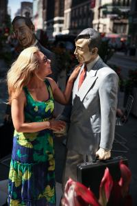 A passerby interacts with a life-like sculpture of an ordinary man by Seward Johnson. (Photo: Laurentiu Garofeanu/Garment District Alliance)