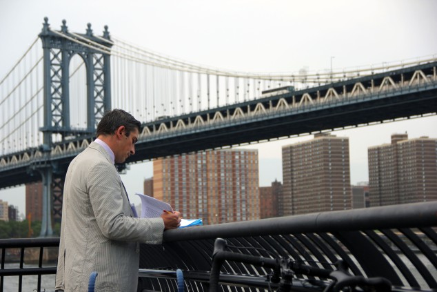 "Poet Richard Blanco scribbles some notes before reading Walt Whitman's ""Crossing Brooklyn Ferry"" at the 20th Anniversary of Poets House's annual walk across The Brooklyn Bridge. (Photo: Justin Joffe/Observer)"