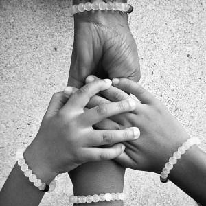 Hands wearing classic Lokai bracelets