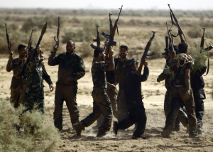 "Shiite Muslim fighters, loyal to Iraqi Shiite cleric Moqtada al-Sadr, take part in a last combat training near the city of Najaf on August 23, 2014, before joining the government forces to fight Islamic State (IS) jihadists in the Jurf al-Sakhr area, south of Baghdad. Iraqi officials worked to calm soaring tensions after the killing of 70 people at a Sunni mosque, as Washington branded the beheading of an American journalist a ""terrorist attack."" AFP PHOTO / HAIDAR HAMDANI (Photo credit should read HAIDAR HAMDANI/AFP/Getty Images)"