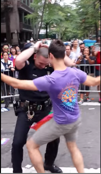 NYPD officer dances with a marcher at the NYC Pride March on Sunday, June 28. (Photo: Youtube/Paige Ponzeka)