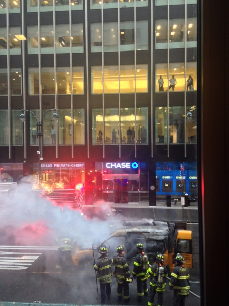 Chase employees look on as FDNY puts out a fire that consumed a New York taxicab.