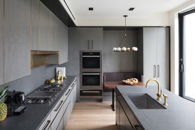 Each kitchen is custom designed by Mr. Juul-Hansen, featuring quarter-sawn white oak millwork, cerused, limed, and stained gray with brass trim.