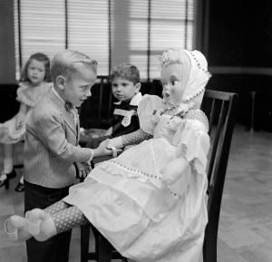 A young boy greets a child size doll which is to be his dancing partner during a dancing lesson. (Photo by Three Lions/Getty Images)