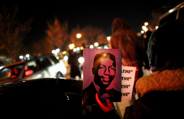 NEW YORK - DECEMBER 3: A protester holds up Garner's photo while walking on the West Side Highway December 3, 2014 in New York. Protests began after a Grand Jury decided to not indict officer Daniel Pantaleo. Eric Garner died after being put in a chokehold by Pantaleo on July 17, 2014. Pantaleo had suspected Garner of selling untaxed cigarettes. (Photo by Yana Paskova/Getty Images)