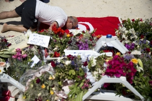 A man kisses a Tunisian flag at the site of a shooting attack on the beach in front of the Riu Imperial Marhaba Hotel in Port el Kantaoui, on the outskirts of Sousse south of the capital Tunis, on June 28, 2015. The Islamic State (IS) group claimed responsibility on June 27 for the massacre in the seaside resort that killed nearly 40 people, most of them British tourists, in the worst attack in the country's recent history. AFP PHOTO / KENZO TRIBOUILLARD        (Photo credit should read KENZO TRIBOUILLARD/AFP/Getty Images)