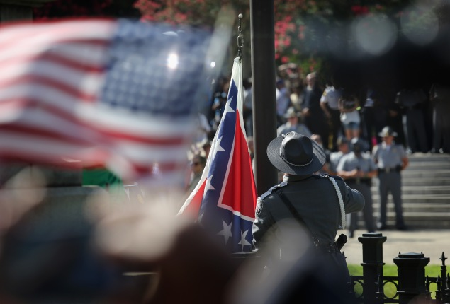 COLUMBIA, SC - JULY 10:  A South Carolina state police honor guard lowers the Confederate flag from the Statehouse grounds on July 10, 2015 in Columbia, South Carolina. Republican Governor Nikki Haley presided over the event after signing the historic legislation to remove the flag the day before.  (Photo by John Moore/Getty Images)