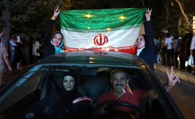 Iranian women wave the national flag during celebration in northern Tehran on July 14, 2015, after Iran's nuclear negotiating team struck a deal with world powers in Vienna. Iranians poured onto the streets of Tehran after the Ramadan fast ended at sundown Tuesday to celebrate the historic nuclear deal agreed earlier with world powers in Vienna. AFP PHOTO/ATTA KENARE        (Photo credit should read ATTA KENARE/AFP/Getty Images)