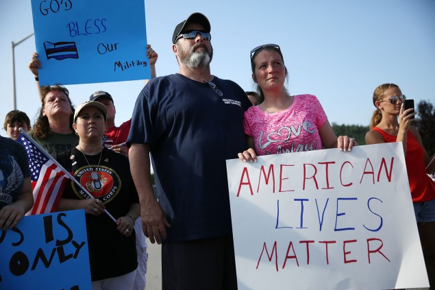 CHATTANOOGA, TN - JULY 19:  Ron Fahy and Misty Fahy hold a sign that reads,' American Lives Matter', as they attend a prayer service near the Armed Forces Career Center/National Guard Recruitment Office which had been shot up on July 19, 2015 in Chattanooga, Tennessee. . The gunman Mohammod Youssuf Abdulazeez, 24, opened fire on the military recruiting station at the strip mall on July 16th and then drove more than seven miles away to an operational support center operated by the U.S. Navy and killed four United States Marines and a Navy sailor.  The gunman was likely killed in a exchange of gunfire with the police. (Photo by Joe Raedle/Getty Images)