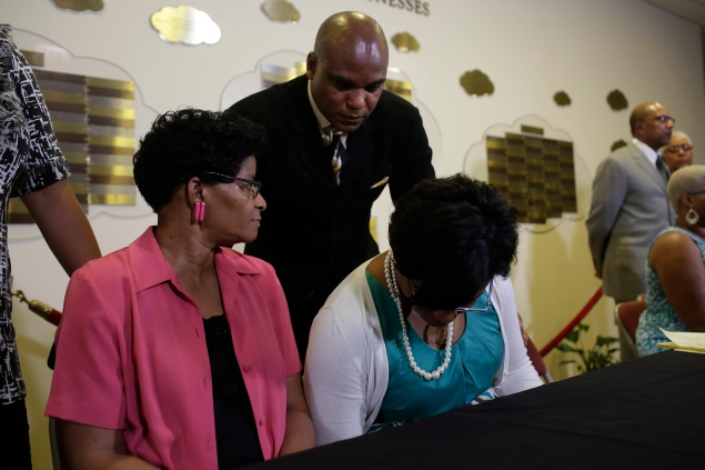 LISLE, IL - JULY 22:  Attorney Cannon Lambert, center, speaks to the mother of Sandra Bland, Geneva Reed-Veal, left, and sister Sharon Cooper, right, before a news conference at DuPage AME Church on July 22, 2015 in Lisle, Illinois. Sandra Bland found dead in her cell at the Waller County Jail after she was found hanging from a plastic bag 3 days after she was pulled over by a Texas State Trooper officer for a traffic violation. (Photo by Joshua Lott/Getty Images)